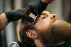 Homme barbu avec la longue barbe obtenant les cheveux élégants rasant, coupe de cheveux, avec le rasoir par le coiffeur dans le r image stock