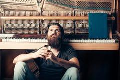 Homme barbu avec le piano en bois proche en verre photo libre de droits