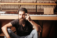 Homme barbu avec le piano en bois proche en verre photos stock