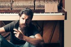 Homme barbu avec le piano en bois proche en verre photographie stock