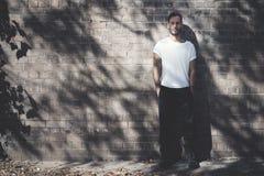 Homme barbu avec le tatouage utilisant le T-shirt blanc vide et les jeans noirs Fond de mur de briques maquette horizontale photographie stock libre de droits