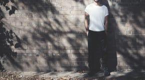Homme barbu avec le tatouage utilisant le T-shirt blanc vide et les jeans noirs Fond de mur de briques Maquette large, ombres photos libres de droits