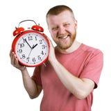 Homme barbu avec un réveil rouge images libres de droits