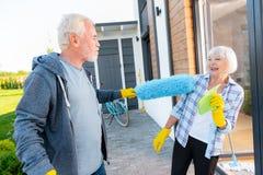Homme barbu ayant l'amusement avec son épouse attrayante tout en faisant le nettoyage photo libre de droits