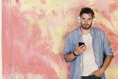 Homme barbu bel américain avec des écouteurs Hippie élégant observé par bleu avec le smartphone images libres de droits