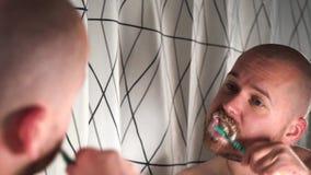 Homme barbu bel dans la brosse à dents d'utilisation de salle de bains et les dents de nettoyage banque de vidéos