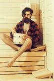 Homme barbu bel dans le bain en bois avec le seau photographie stock