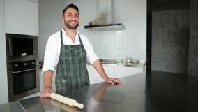Homme barbu bel dans le tablier posant dans la cuisine Il regarde si heureux banque de vidéos