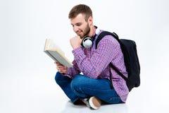 Homme barbu bel gai avec le sac à dos et le livre de lecture d'écouteurs Image stock