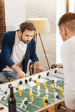 Homme barbu bel jouant le football de table Images stock