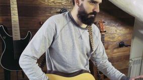 Homme barbu bel jouant le mouvement lent de guitare acoustique banque de vidéos