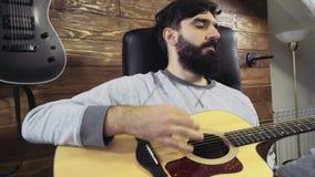 Homme barbu bel jouant le mouvement lent de guitare acoustique clips vidéos