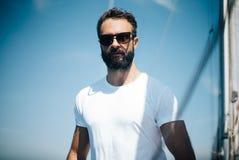 Homme barbu bel se tenant sur un yacht image stock
