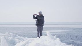 Homme barbu blond bel en verres dans la position chaude de veste d'hiver sur le bloc de glace au glacier prenant la photo clips vidéos
