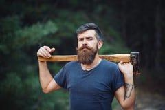 Homme barbu brutal avec une moustache intelligente avec une hache dans des ses mains dans les bois photographie stock