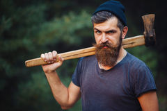 Homme barbu brutal avec une moustache intelligente avec une hache dans des ses mains dans les bois Image stock