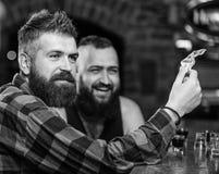 Homme barbu brutal de hippie d?penser des loisirs avec l'ami au compteur de barre Hommes d?tendant ? la barre Amiti? et loisirs V photo libre de droits