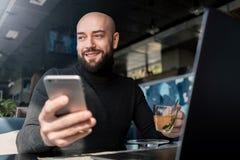 Homme barbu chauve dans le fonctionnement noir de col roul? sur l'ordinateur portable, tenant le smartphone tout en se reposant e images libres de droits