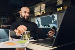 Homme barbu chauve dans le fonctionnement noir de col roul? sur l'ordinateur portable, tenant le smartphone tout en se reposant e photo stock