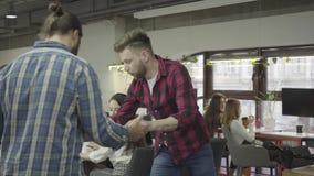 Homme barbu concentré étudiant des documents sur papier se tenant dans le bureau Jeune collègue montant le vélo dans le bureau banque de vidéos