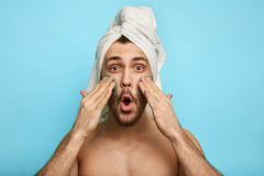 Homme barbu décontracté appliquant un masque sur sa joue photos libres de droits