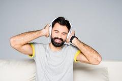 Homme barbu dans des écouteurs blancs Image libre de droits