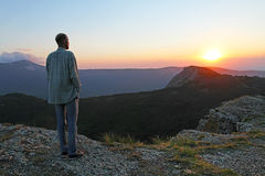 Homme barbu dans des jeans regardant le coucher du soleil dans le solt de montagnes Photographie stock libre de droits