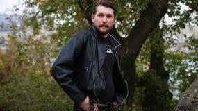 Homme barbu dans des vestes en cuir noires dans une forêt Images stock
