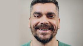Homme barbu dans la bonne humeur riant chaleureusement, plan rapproché de visage, émotions positives banque de vidéos