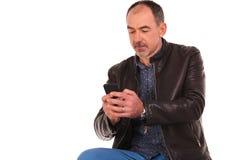 Homme barbu dans la pose de veste en cuir assis Photos libres de droits