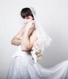 Homme barbu dans la robe de mariage d'une femme sur son corps nu, participation une fleur sur sa tête un voile jeune mariée barbu images libres de droits