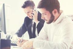 Homme barbu dans le bureau avec son colleauge au téléphone images stock