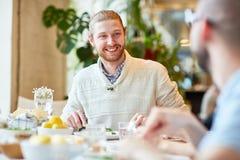 Homme barbu dans le chandail se reposant avec des amis en café Photo stock