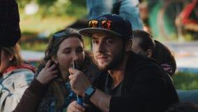 Homme barbu dans le chapeau riant avec ses amis et narguilé de tabagisme dehors en parc banque de vidéos