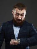 Homme barbu dans le costume attendant et regardant l'horloge images stock