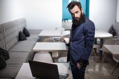Homme barbu dans le costume avec l'ordinateur portable et la tasse de café en café ; Photos libres de droits