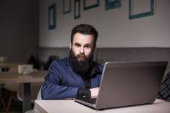 Homme barbu dans le costume et avec l'ordinateur portable se reposant en café et passant en revue Images libres de droits