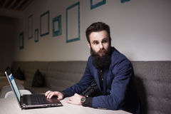 Homme barbu dans le costume et avec l'ordinateur portable se reposant en café et passant en revue Image libre de droits