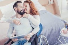 Homme barbu dans les yeux fermants d'un fauteuil roulant tandis que son épouse l'étreignant Image libre de droits