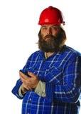 Homme barbu dans un casque antichoc avec un téléphone intelligent Image libre de droits