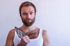 Homme barbu dans un T-shirt avec un vobla sur un fond blanc Image stock