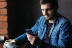 Homme barbu dans une chemise de denim utilisant le téléphone à l'intérieur d'un restaurant tout en buvant d'un café photographie stock libre de droits