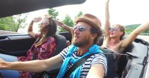 Homme barbu de hippie avec le chapeau conduisant et chantant avec des amis dans le convertible banque de vidéos