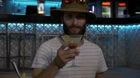 Homme barbu de hippie flirtant et goûtant un cocktail délicieux dans une nuit de fantaisie de barre avec des amis banque de vidéos