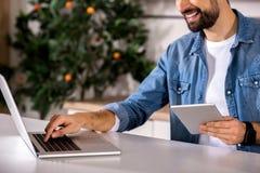 Homme barbu de sourire à l'aide de son ordinateur portable photographie stock