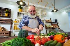 Homme barbu de sourire dans une bonne humeur préparant la nourriture pour le dîner photographie stock