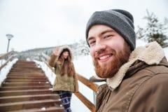 Homme barbu de sourire marchant avec son amie dans la forêt d'hiver Image libre de droits