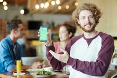 Homme barbu de sourire tenant Smartphone Images libres de droits