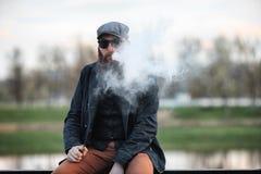 Homme barbu de Vape dans la vie réelle Portrait de jeune type avec la grande barbe dans un chapeau et des lunettes de soleil vapi image libre de droits