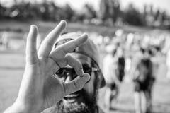 Homme barbu devant le fond de rive de foule Festival d'été de billet de livre à l'avance Fest de visite de hippie images libres de droits